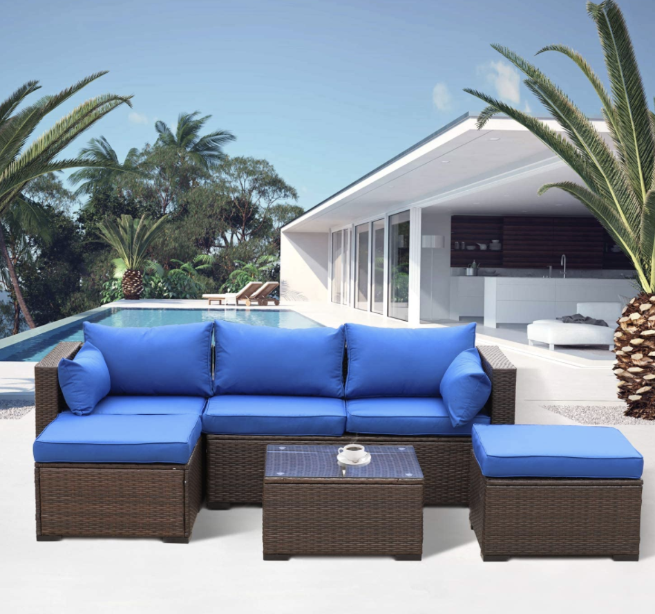A blue four-piece patio furniture set with sectionals and a small wicker table