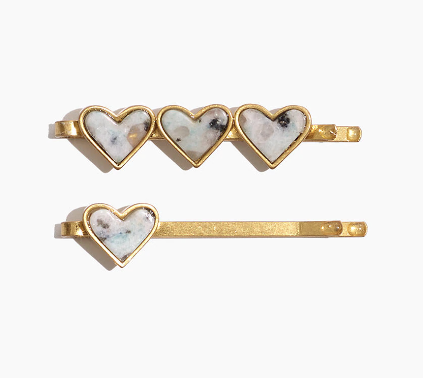 two gold hair pins: one has three hearts on it in a mixture of colored stones while the other has a single heart