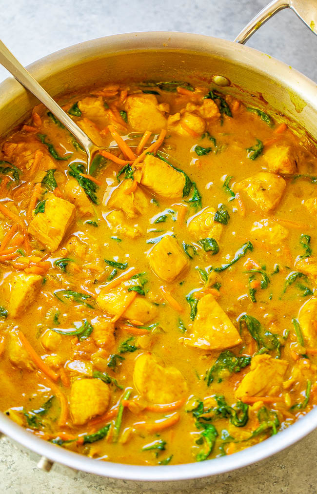 A bowl of yellow coconut curry chicken with spinach and carrots.