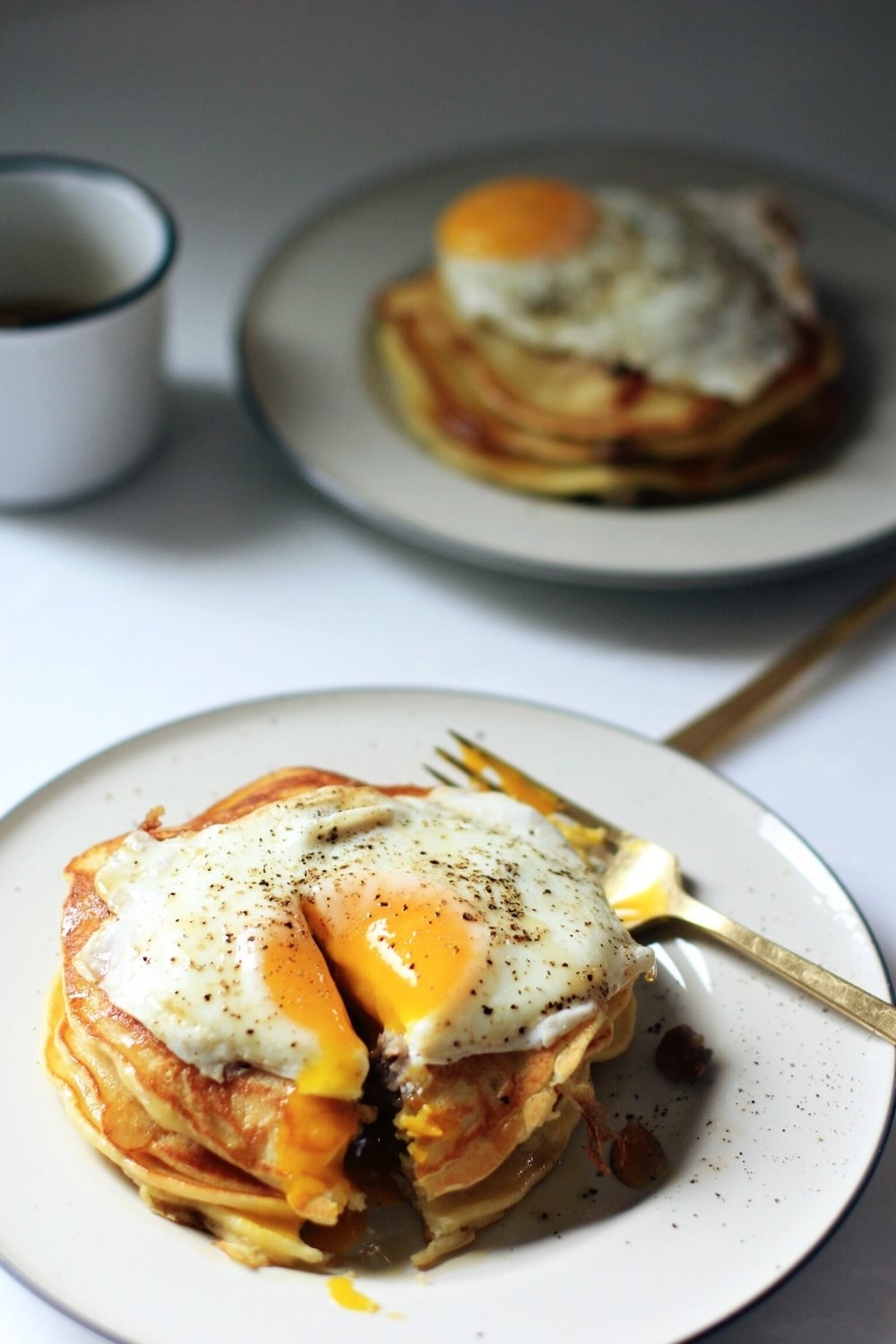 A stack of pancakes with fried egg on top.