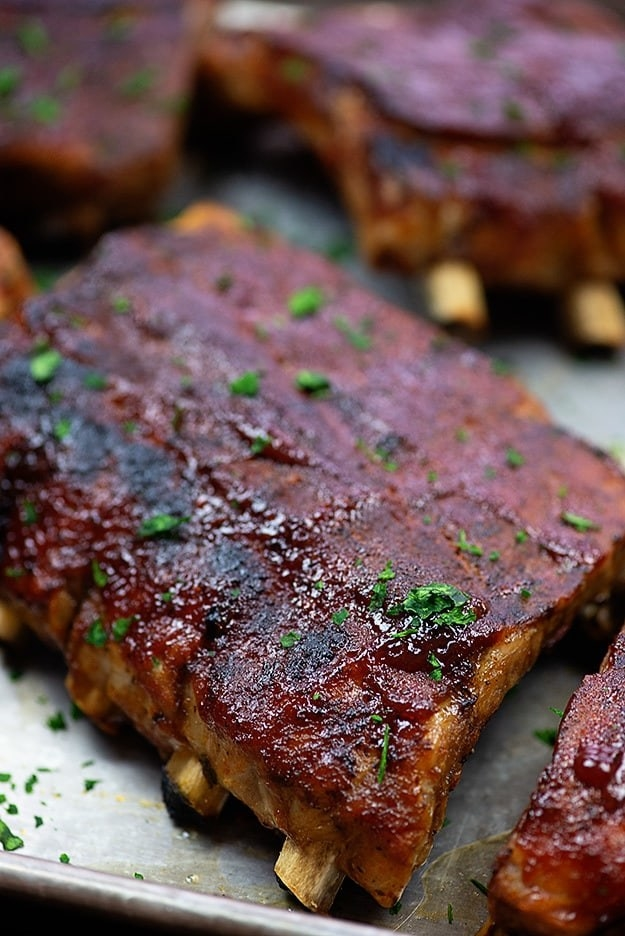 A baking sheet topped with crispy glazed BBQ ribs.