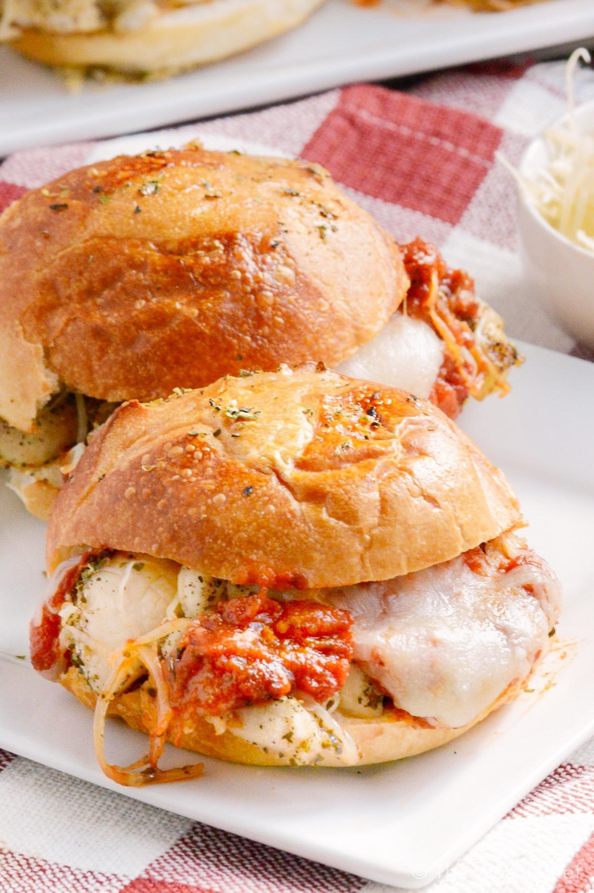 Two sliders stuffed with cheesy chicken Parmesan and tomato sauce.