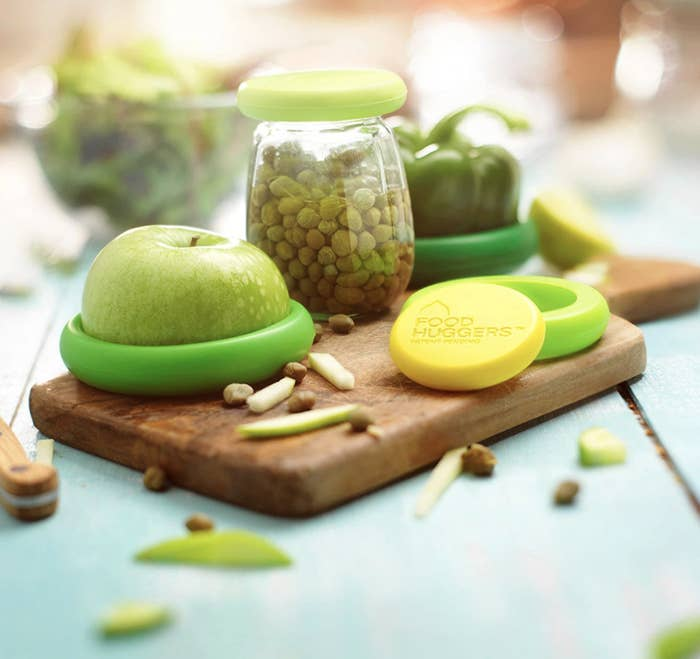 Green reusable food huggers on half an apple and jar of capers