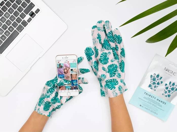 model wearing leaf-covered gloves scrolls through instagram