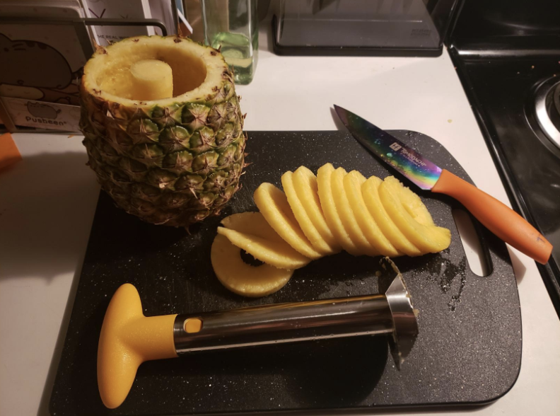 A cored pineapple next to perfectly chopped fruit
