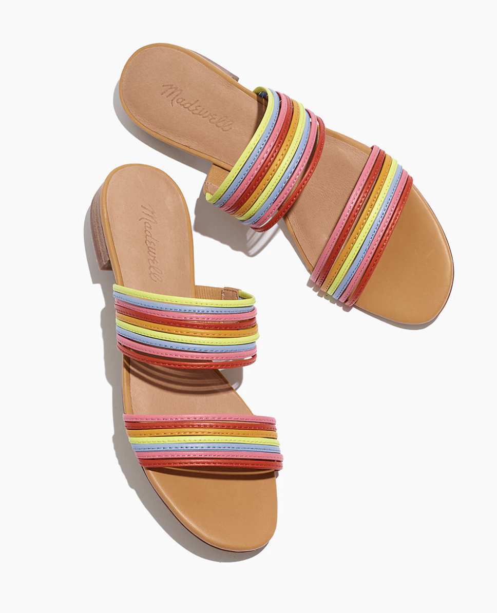 slip on sandals with two bands that go around the foot, each band has a strip of pink, red, orange, pink yellow, and blue