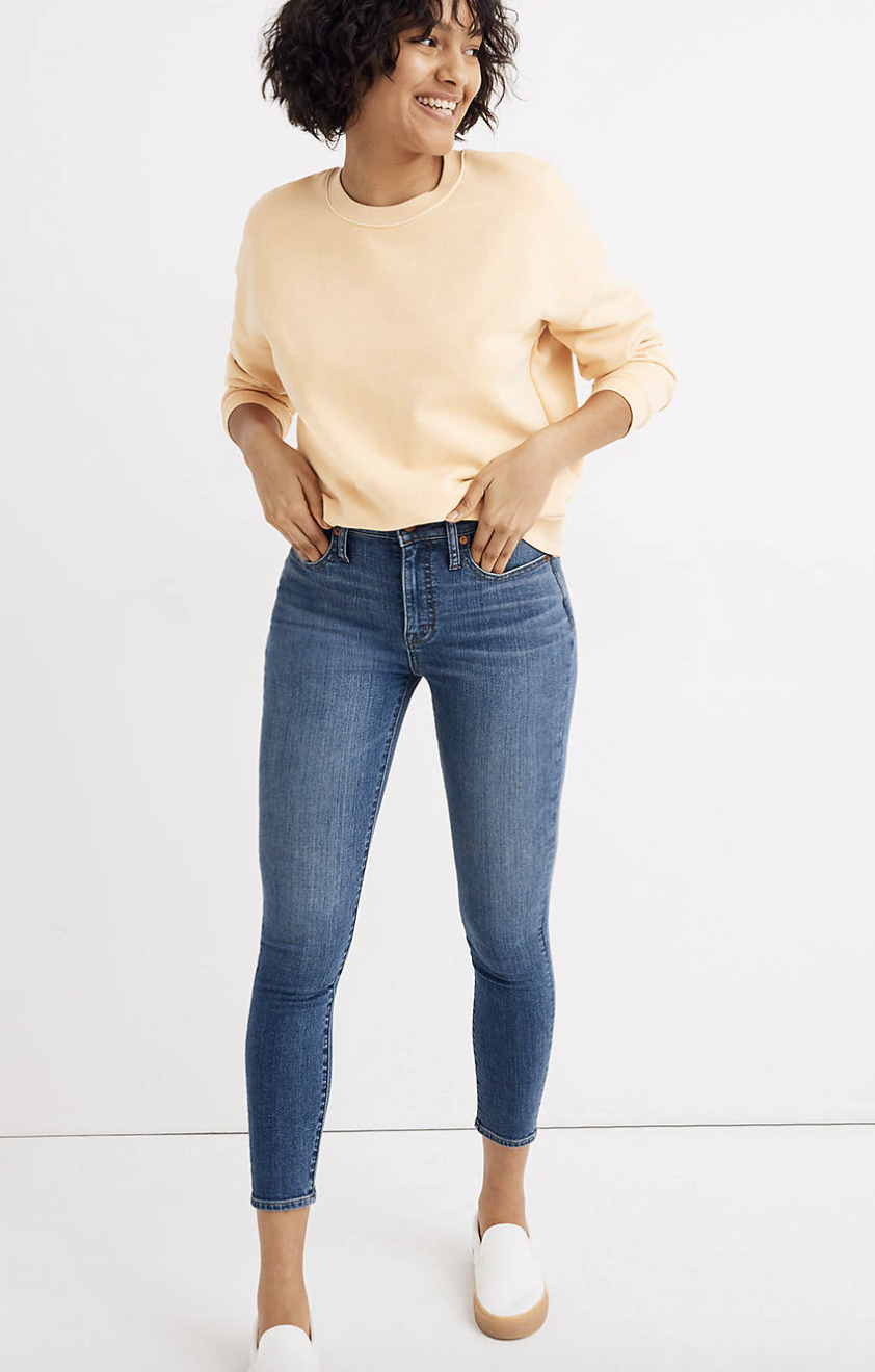 a model wearing medium blue ankle cropped jeans