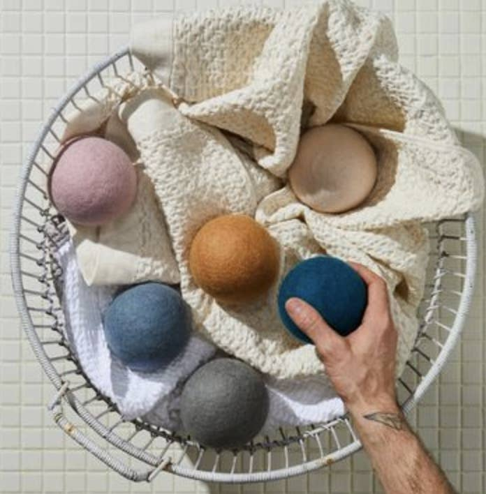 A model holds a blue dryer ball above a laundry bin filled with towels