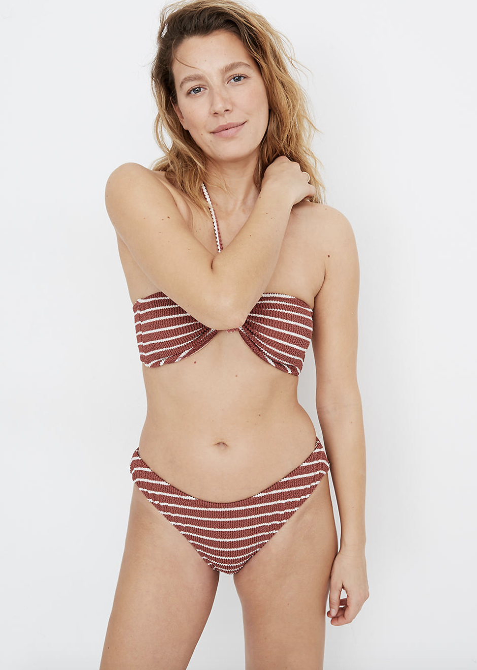 a model wearing a textured burgundy bandeau bikini top with white vertical stripes and matching bottoms