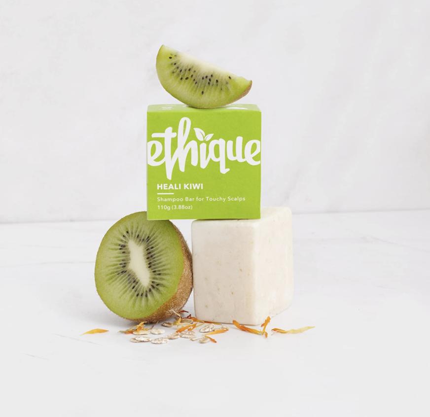A Ethique Heali Kiwi white shampoo bar next to a kiwi