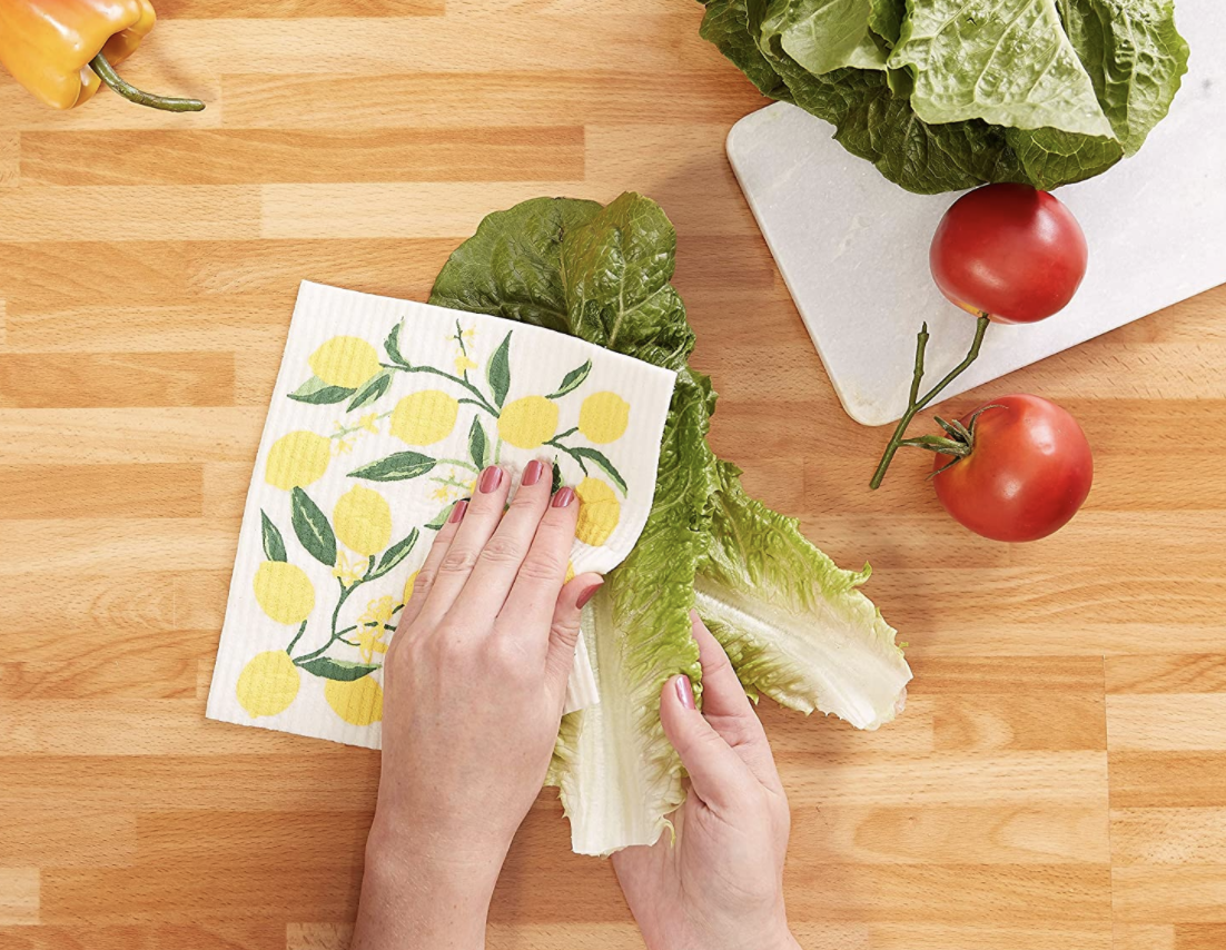 A model uses a lemon-printed Swedish dishcloth to dry off a piece of lettuce