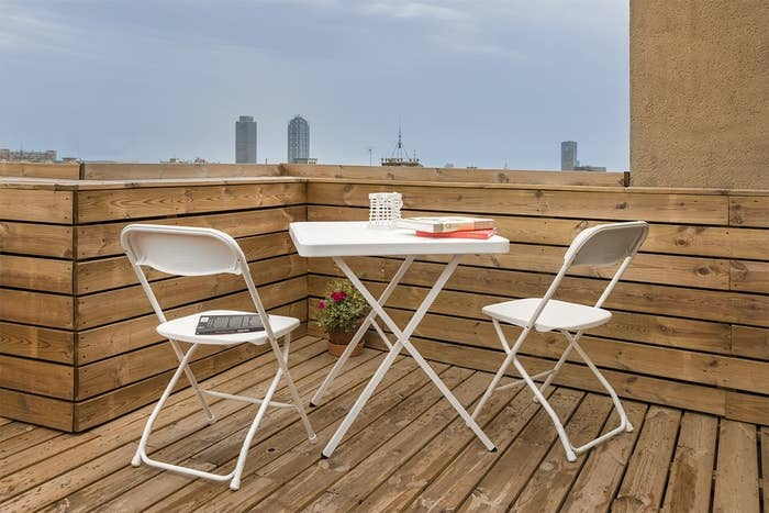 Two white chairs and table set up on a wooden deck on a high-rise building.
