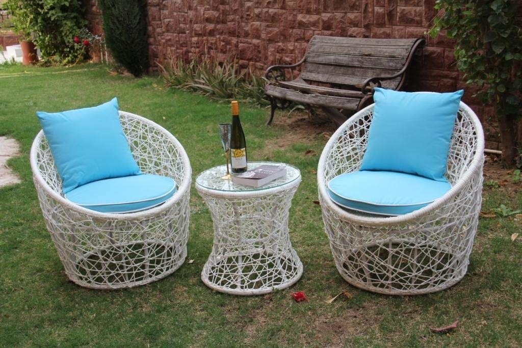 Two wicker chairs with blue seat cushions and pillows with a round table between them.