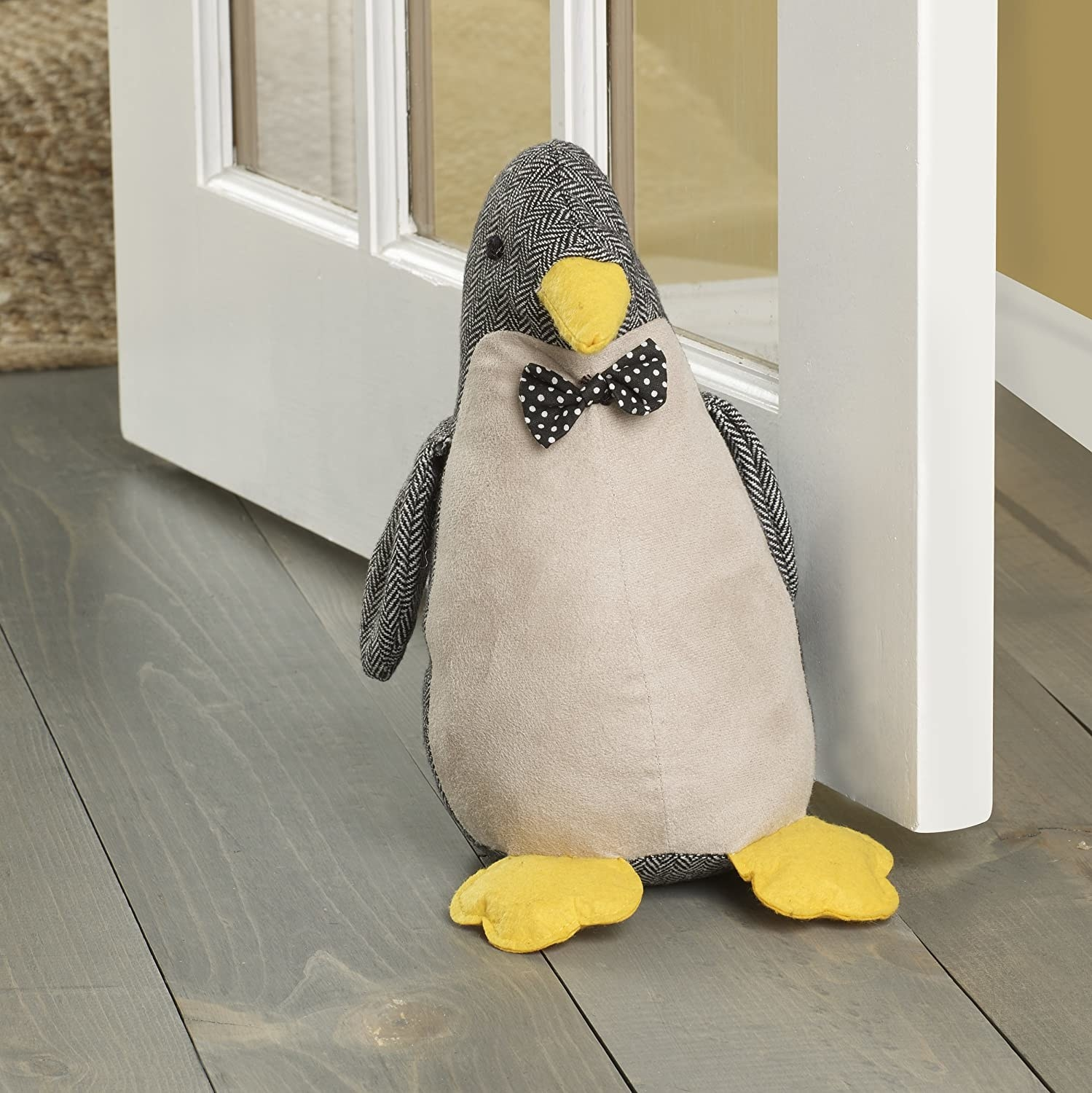 A penguin with a bowtie is on the ground holding a door open