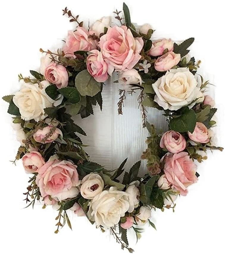 A wreath with lush flowers hangs on a door