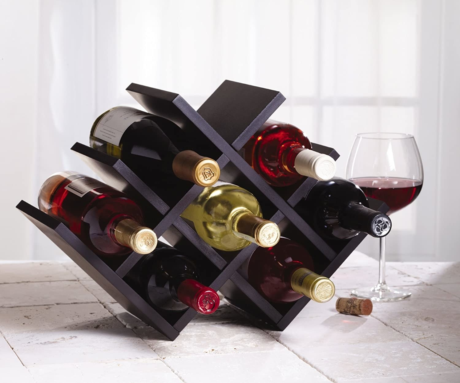 A winerack sits on a table with wine bottles in it and a glass of red wine beside it