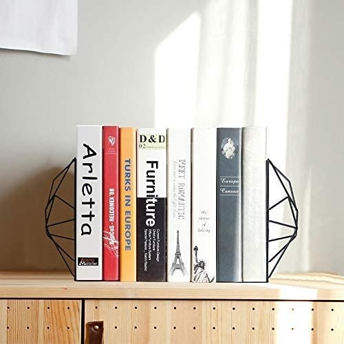 Two geometrical bookends hold together books on a table
