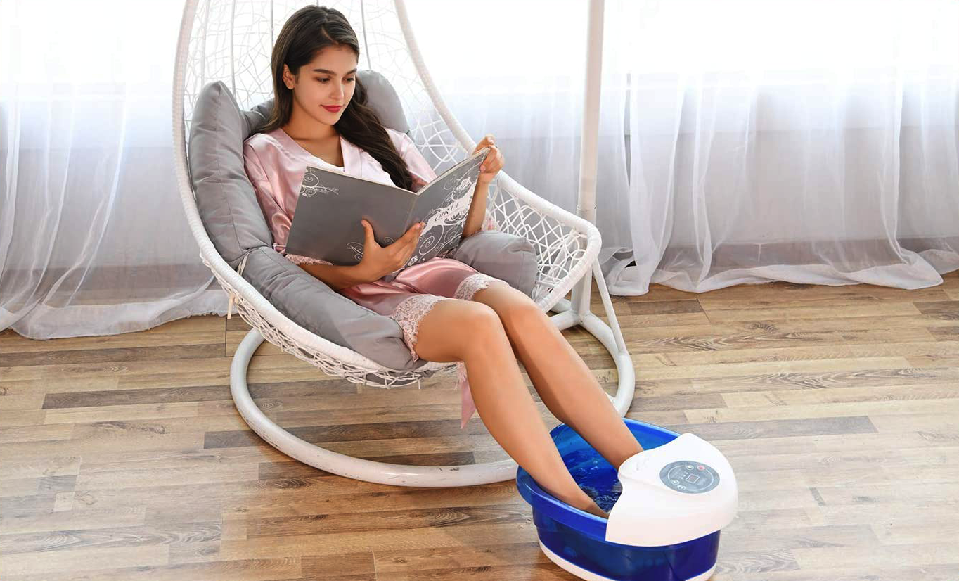 A person reads a book while using he foot spa