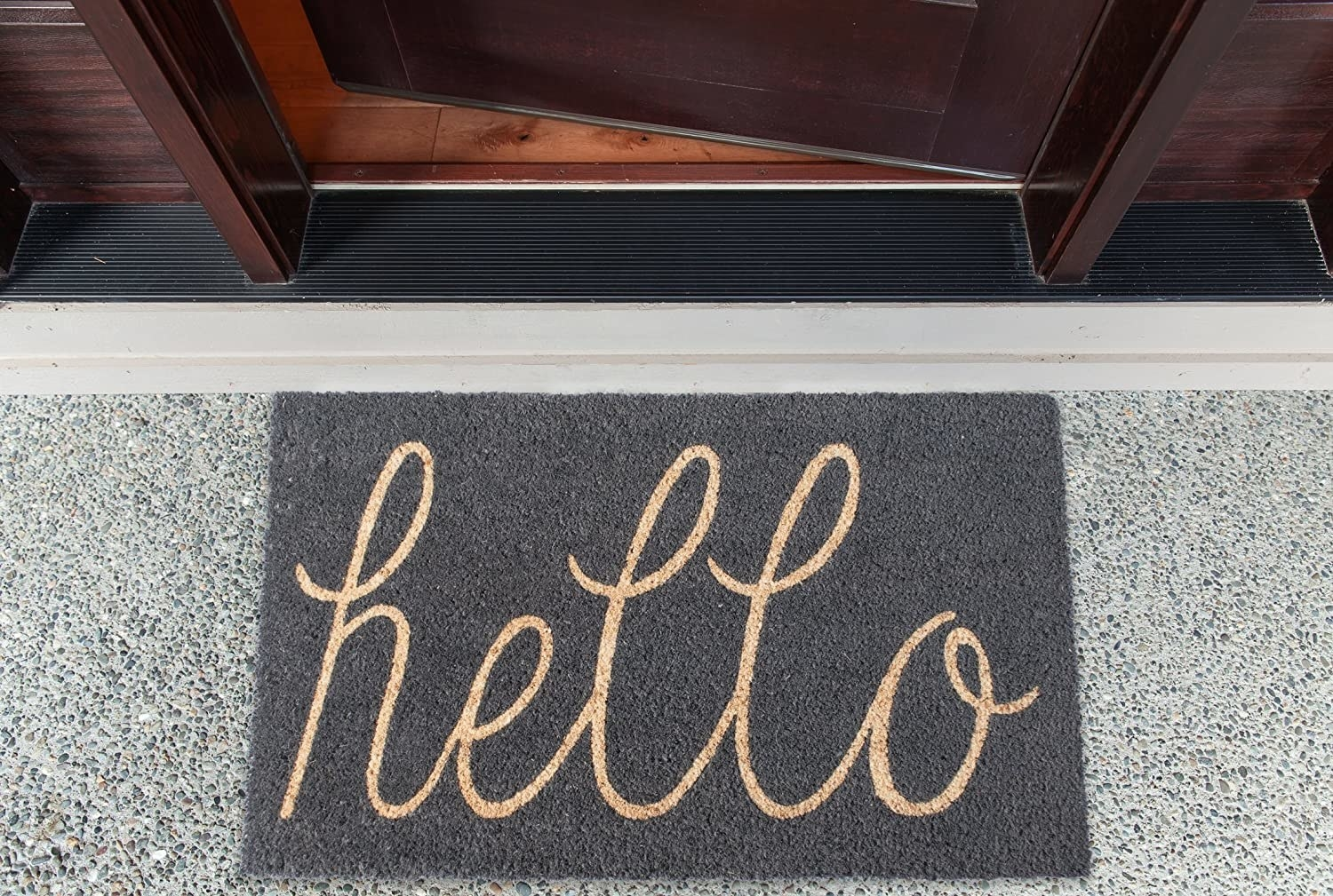 A mat that says hello is on the ground in front of a partially opened door