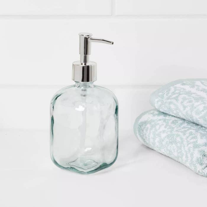 A transparent glass soap dispenser