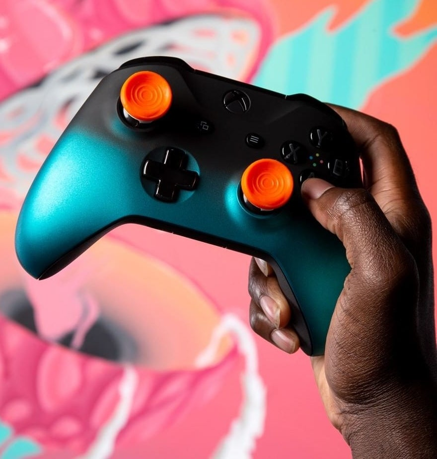 A person holding up a PlayStation 4 controller with performance thumbsticks