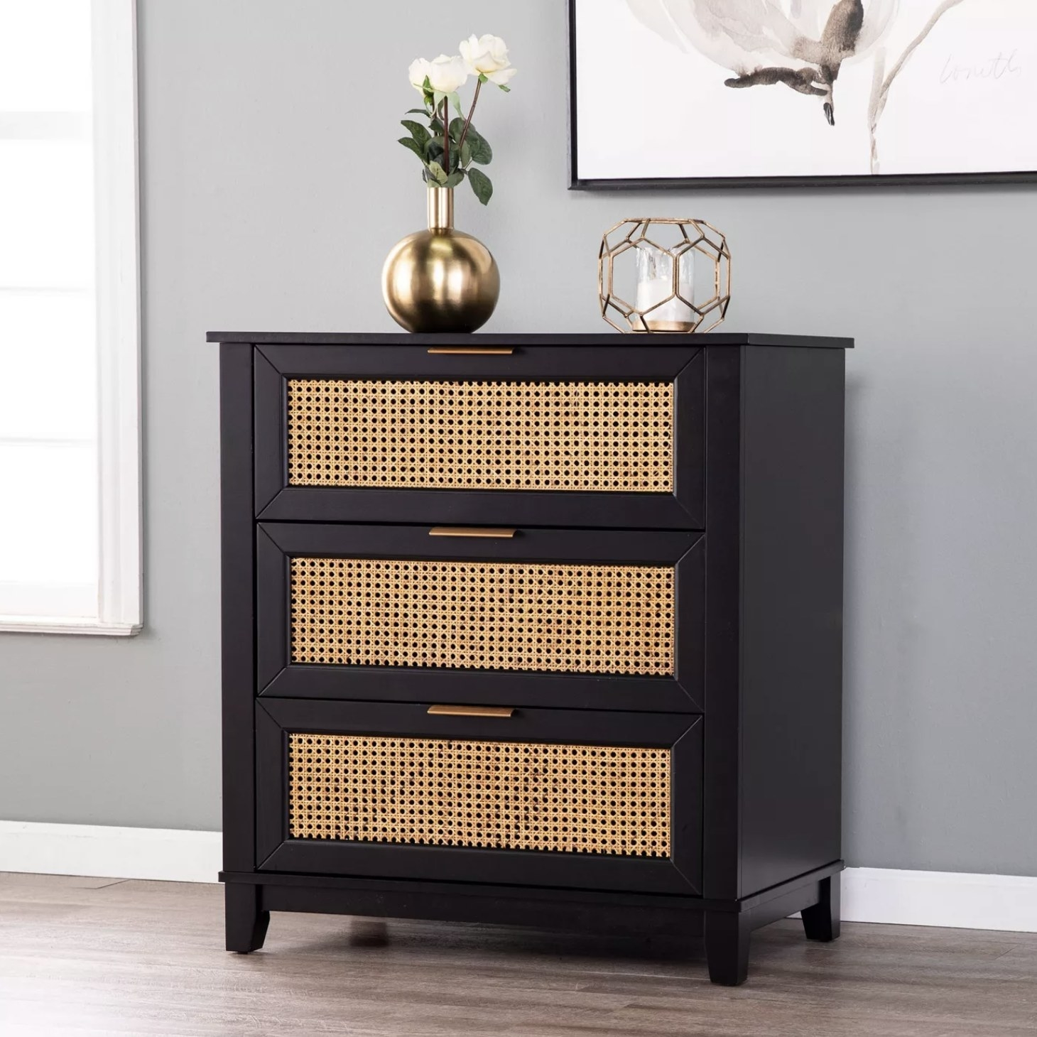 A black dresser with wicker paneling
