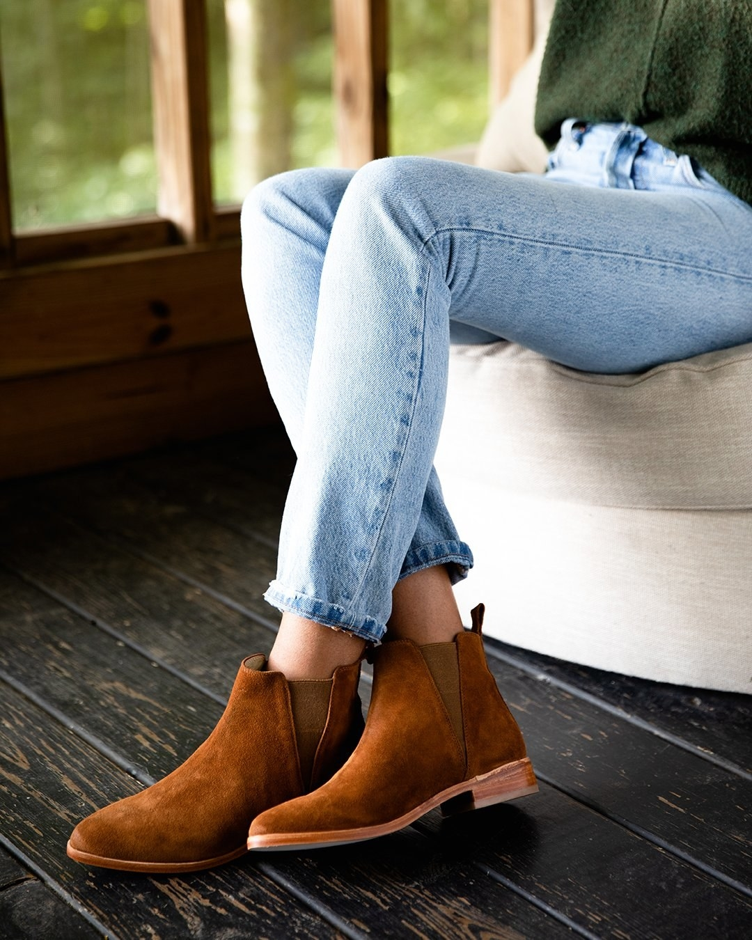 Model wearing a pair of brown suede Chelsea boots