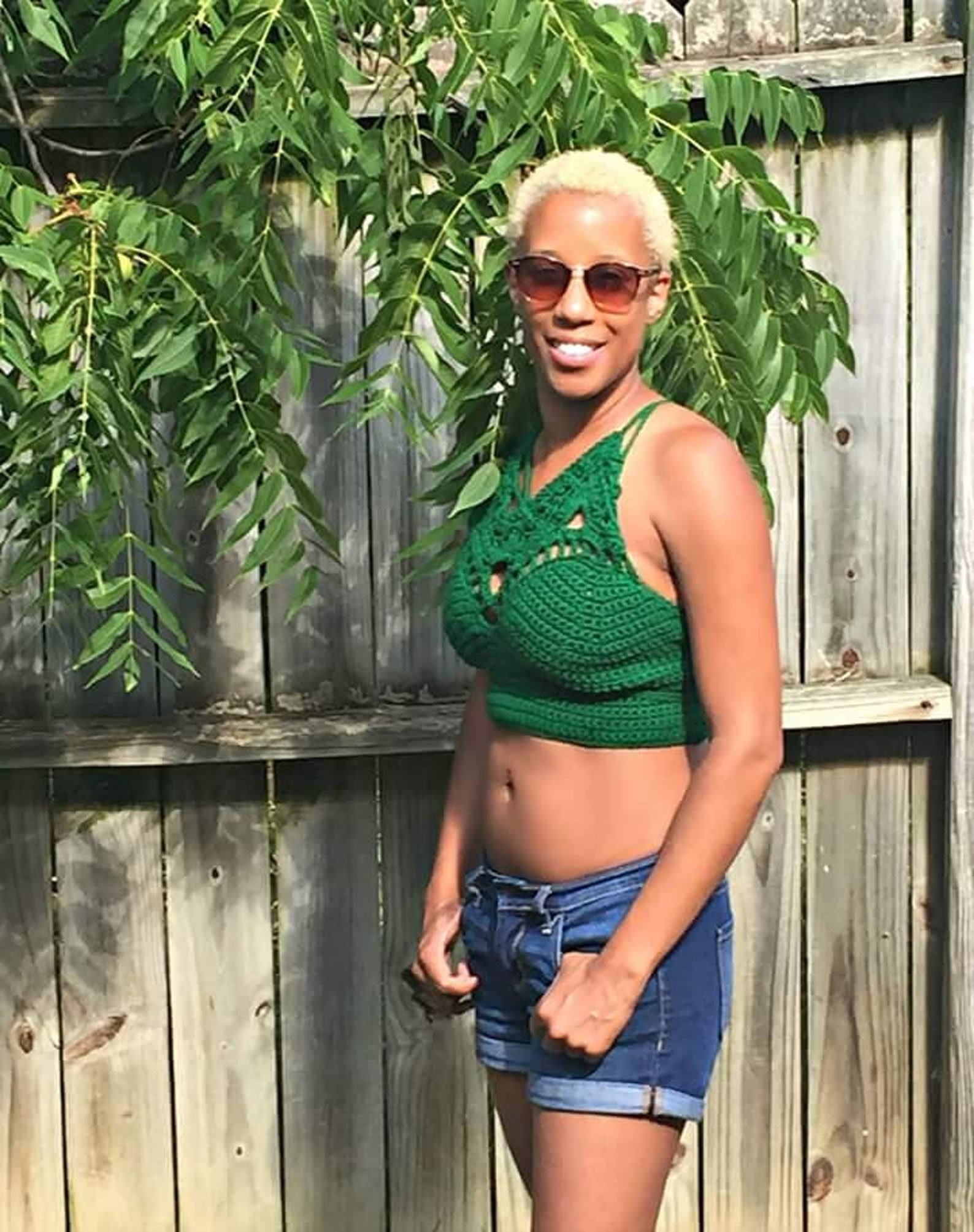 A person wearing a green crop top with a crochet pattern