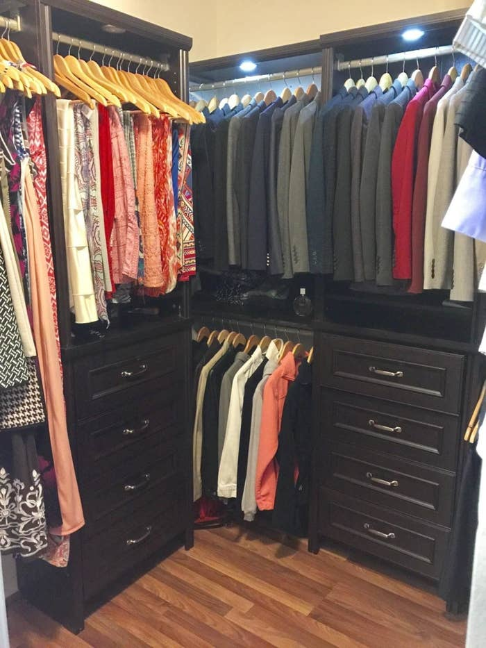 Reviewer photo of a nicely organized closet with circular lights attached to the top, illuminating all the clothes