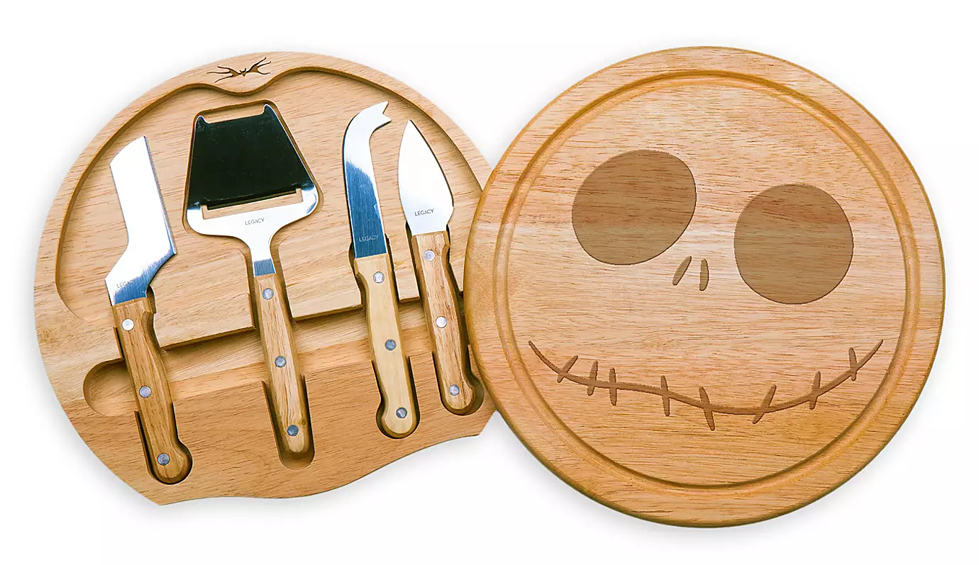 An opened cheese board with the face of Jack Skellington and four utensils