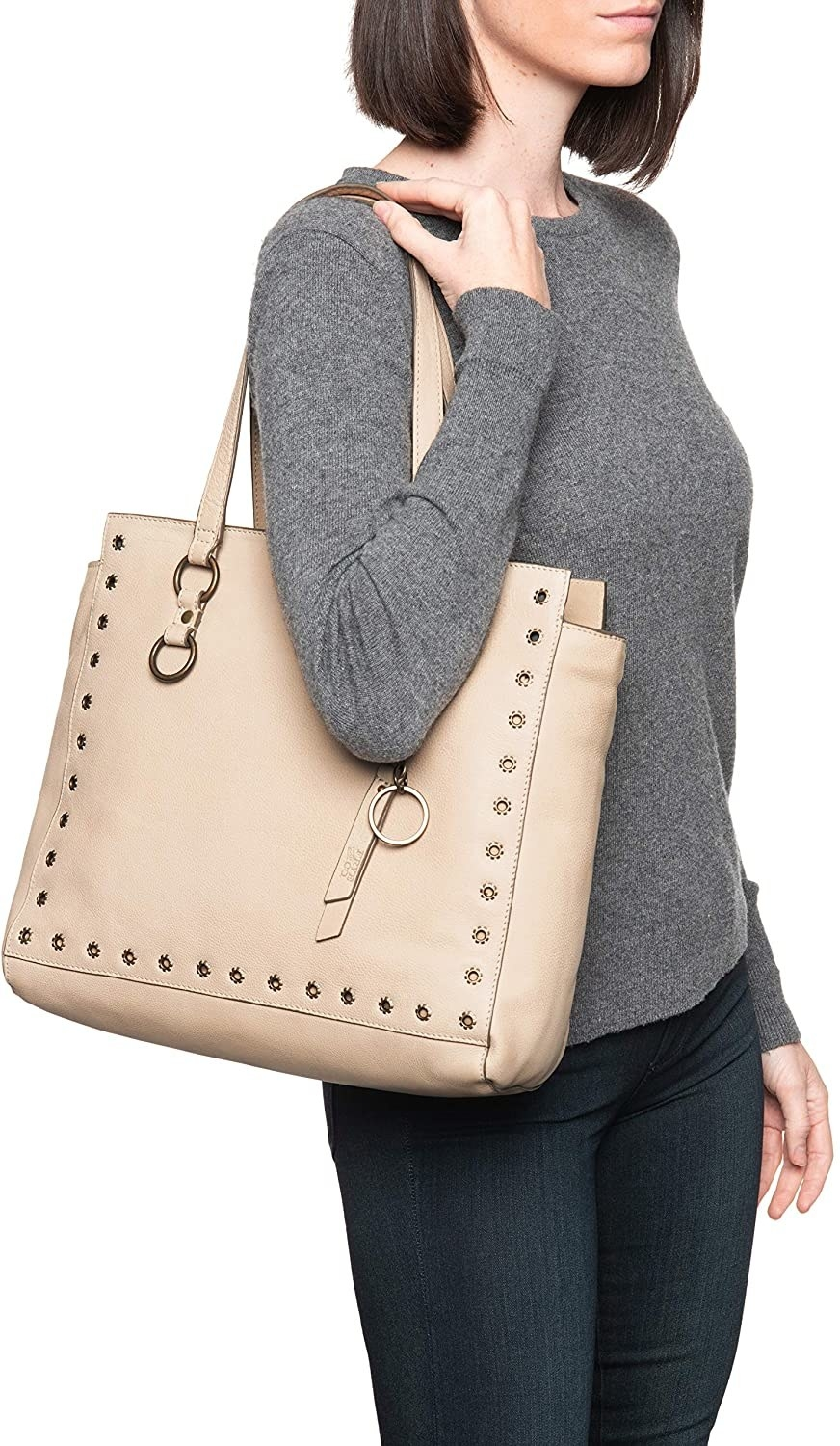 Model wearing the purse over their shoulder showing the eyelet detailing around the outside and key rings on the side