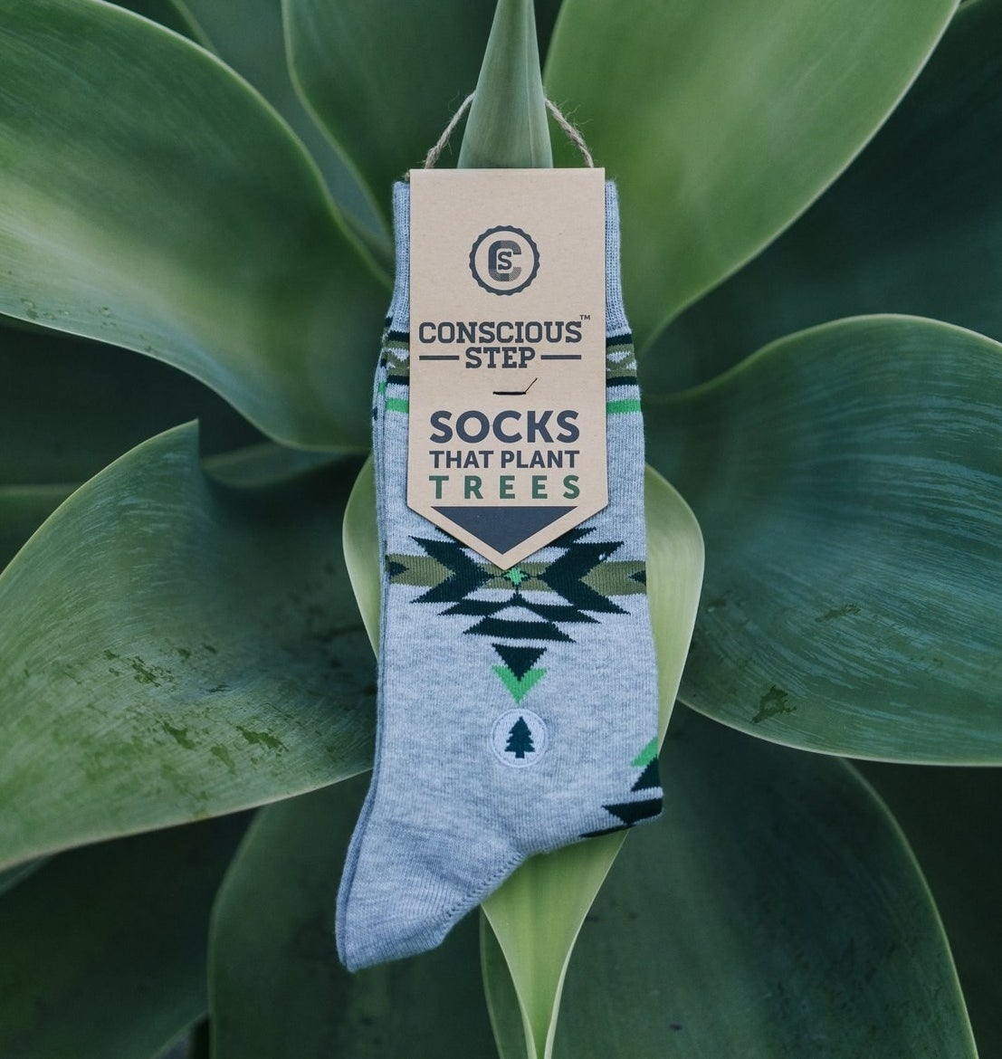 A pair of light gray socks with a design sitting atop a plant