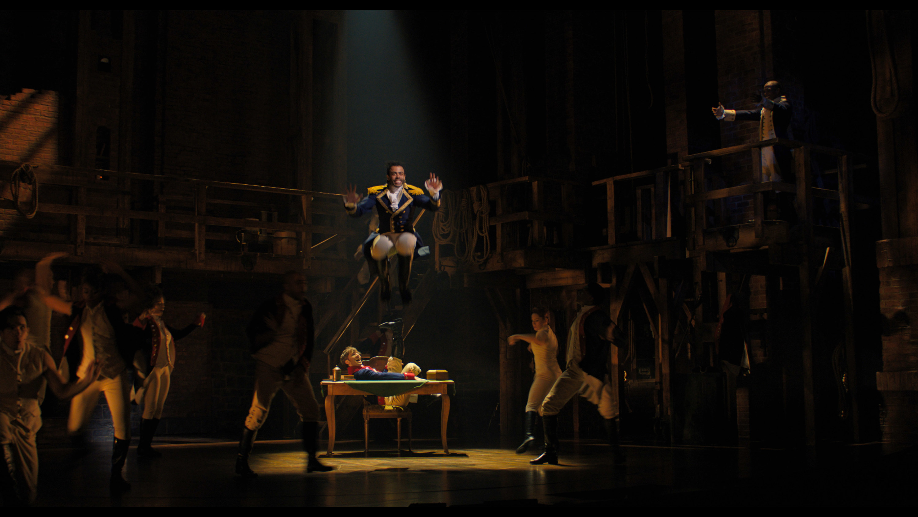 Daveed Diggs jumping off a table and performing in Hamilton