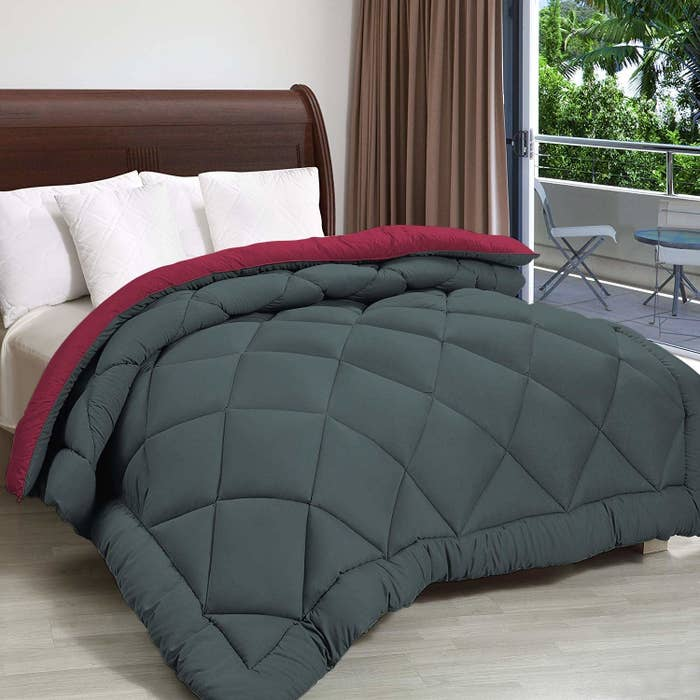 A grey and maroon reversible comforter