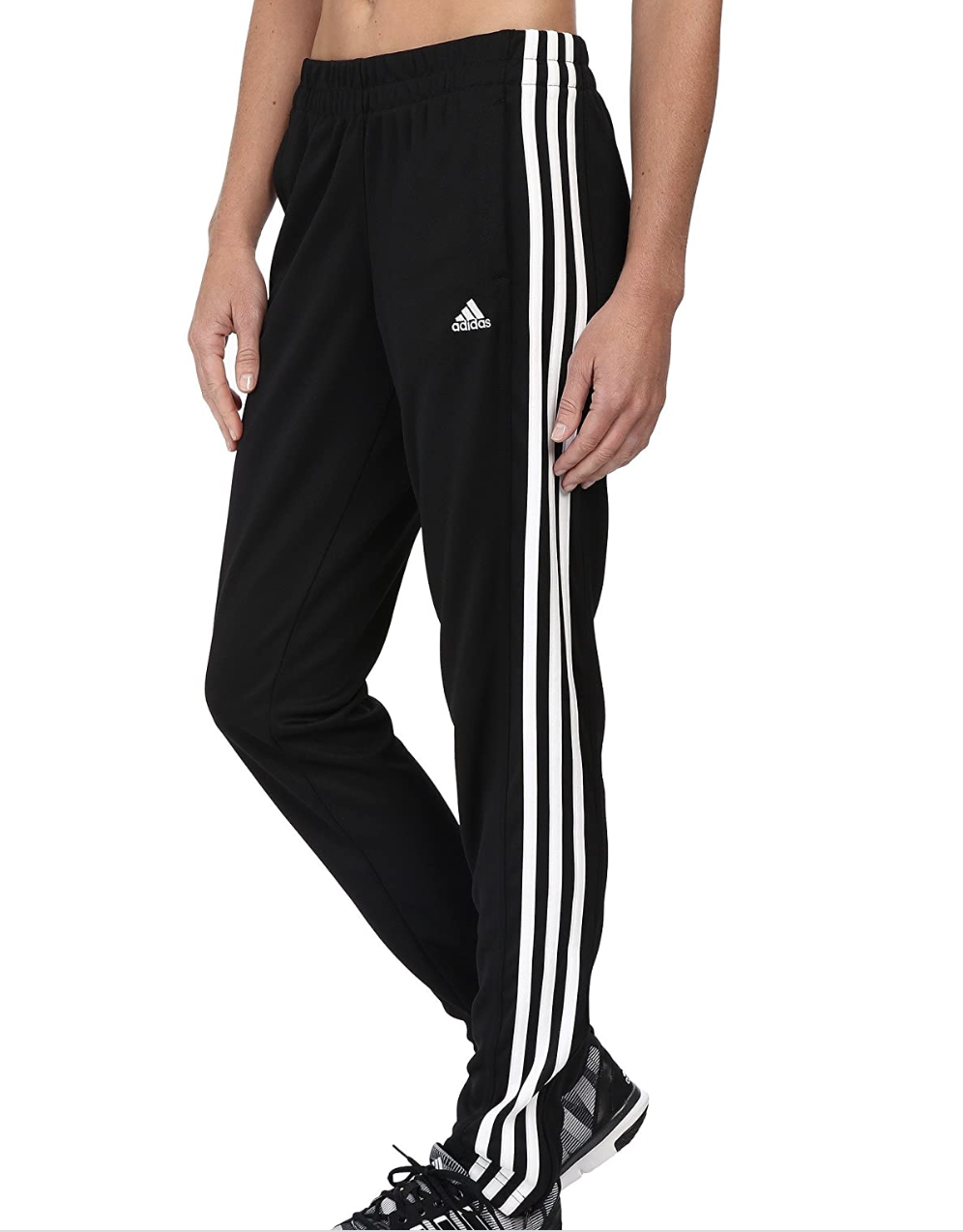 A model in black track pants with three white stripes on the side