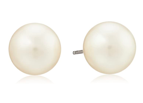 A pair of large round pearl earrings are on a plain background