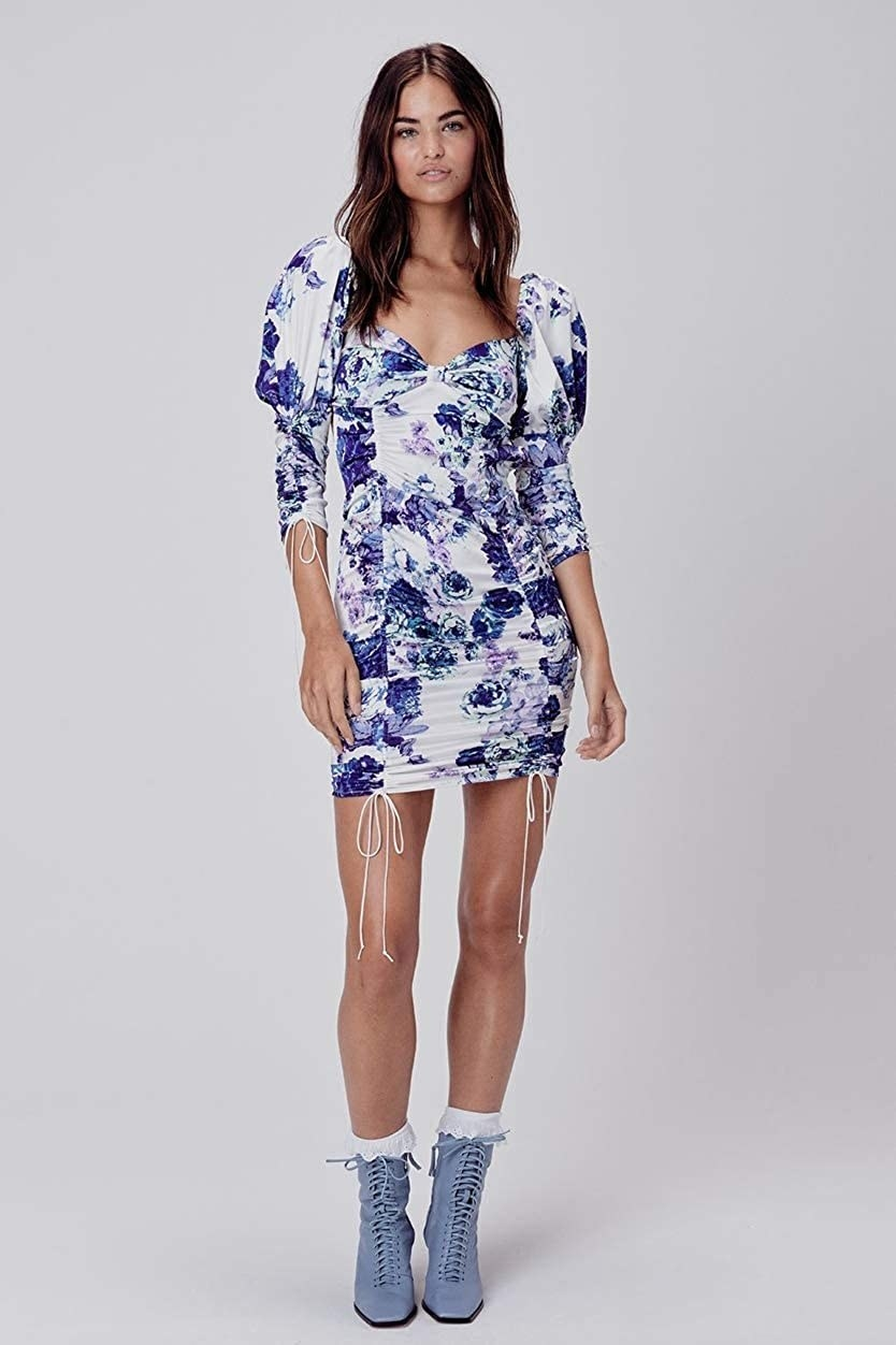 Model wearing the bodycon dress with puff sleeves, sweetheart neckline, drawstrings on the sleeves and skirt, in white with blue and purple floral pattern