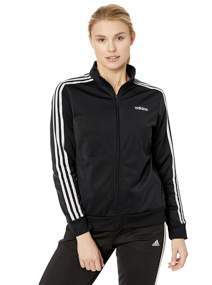 A model in a zip up black track jacket with white stripes on the sleeves