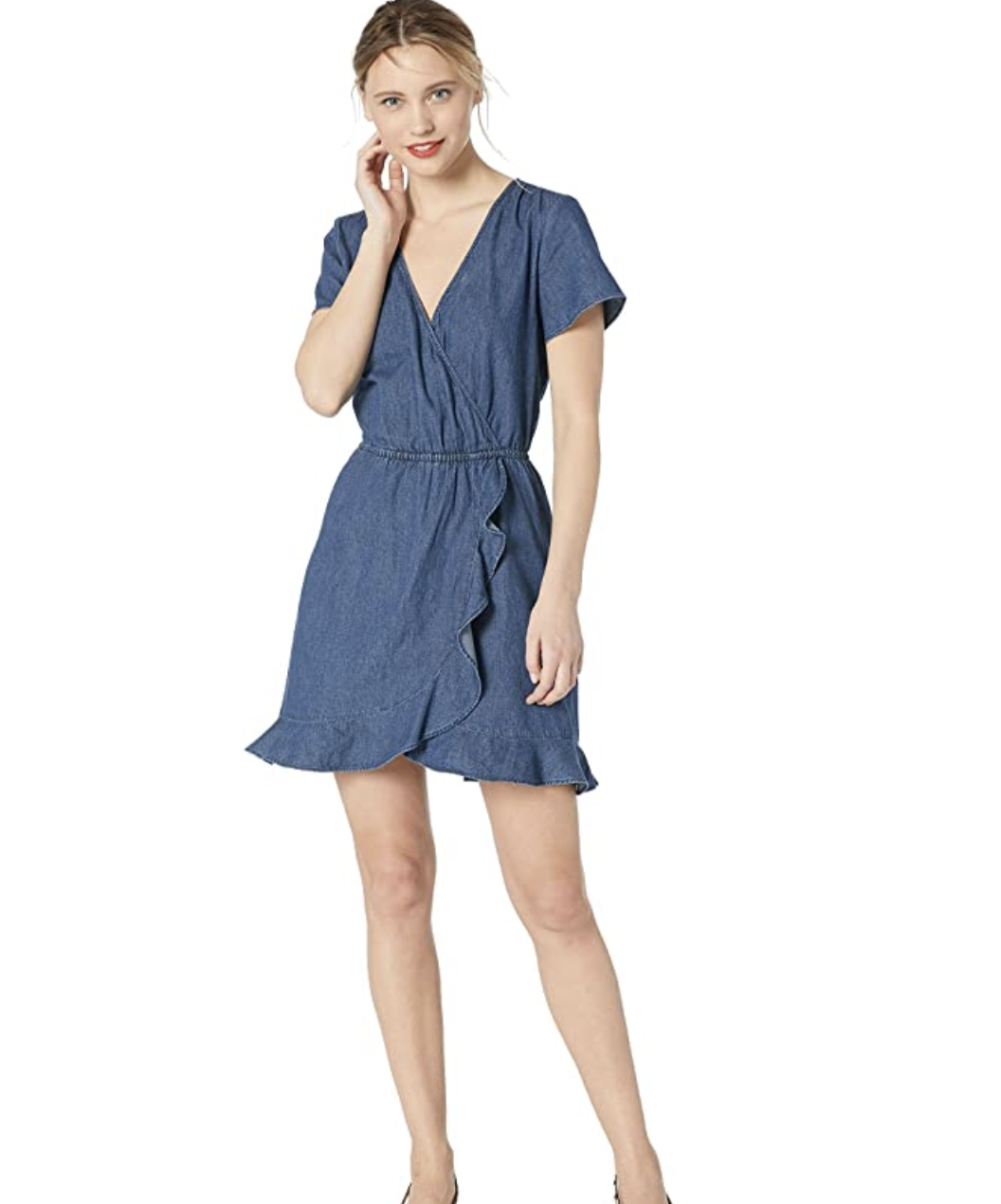 A model in a short-sleeved chambray wrap dress with a V-neck and a ruffled hem  that falls mid-thigh