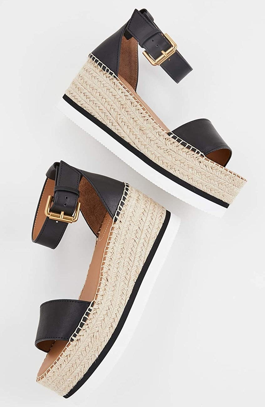 The platform espadrilles with braided tan platform, white sole with black strip, black strap across the foot and black ankle strap