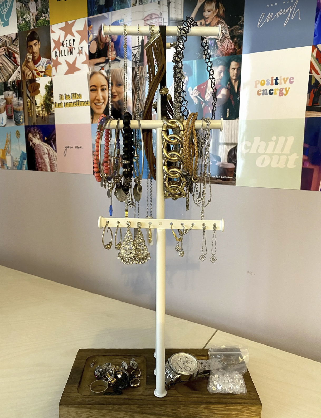 BuzzFeed writer Sam Wieder's jewelry tree full of jewelry neatly placed on it. It has three tiers for hanging and a tray at the bottom for other pieces.