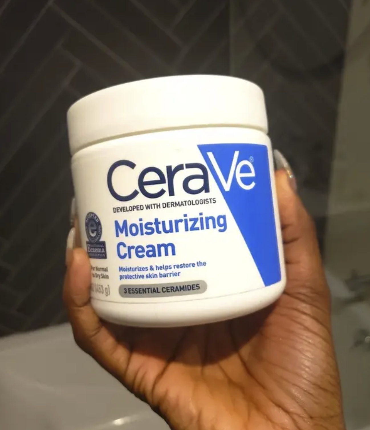 A person holding the tub of moisturizer