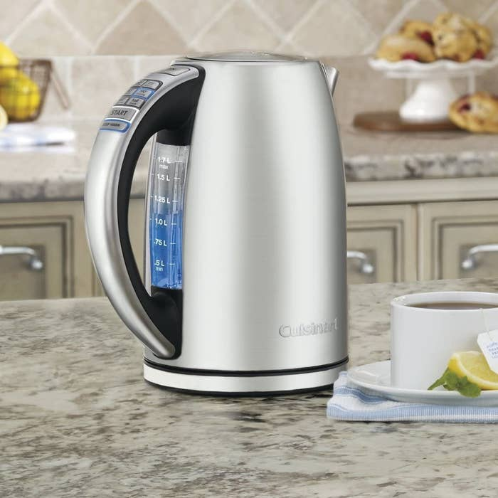 a stainless steel kettle with water measurements on the side and temperature indicating buttons