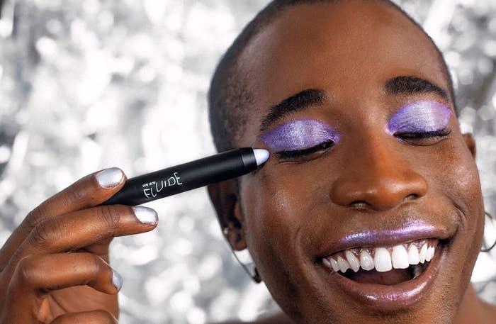 A model applying a purple universal crayon