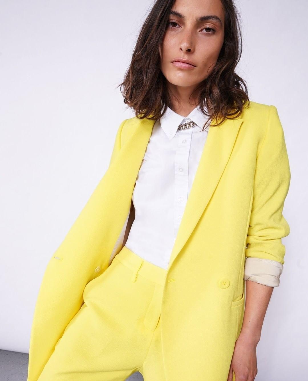 A model wearing a yellow pantsuit
