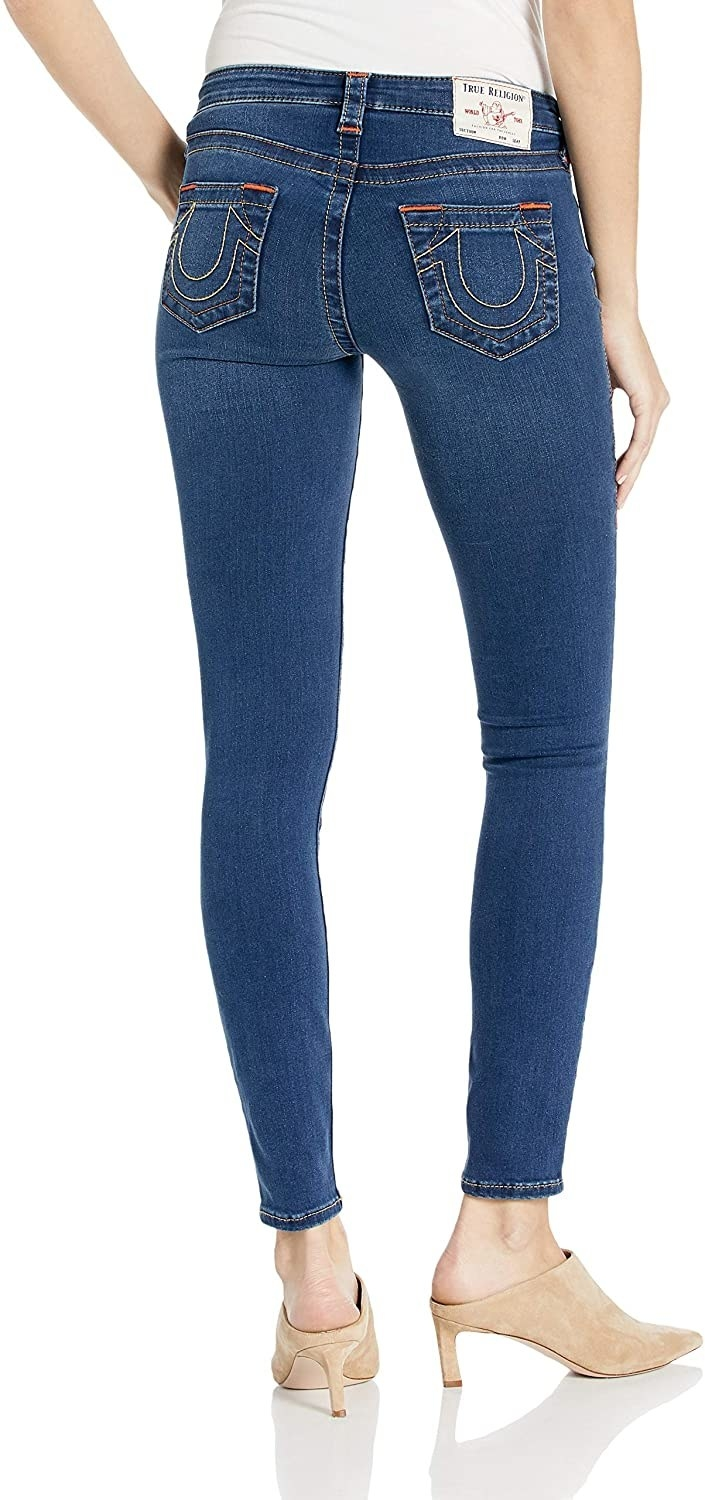 model shows skinny jeans with classic true religion horseshoe stitching on back pockets
