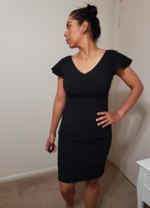 Reviewer wears a black flutter-sleeve dress in their house