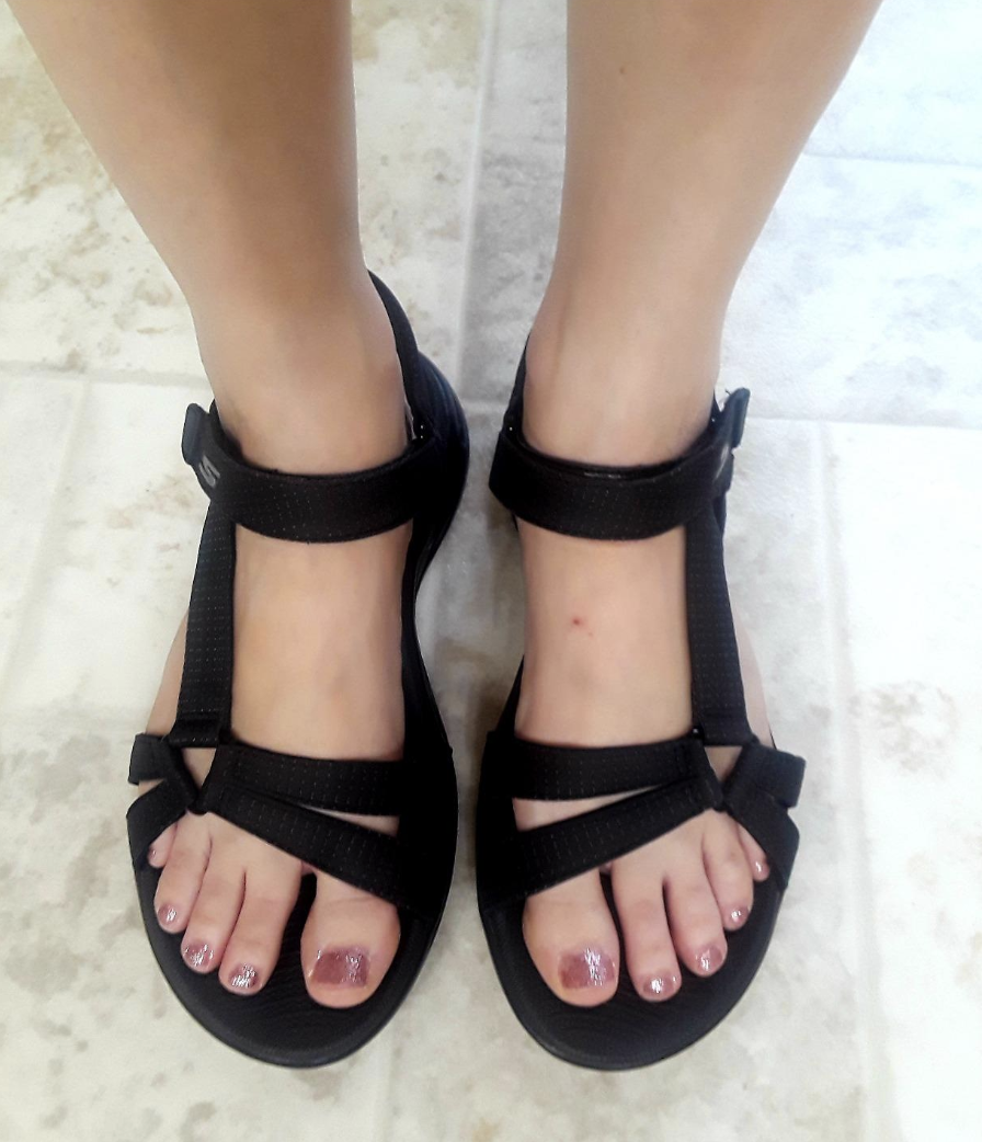 A reviewer's feet in back strappy velcro sandals