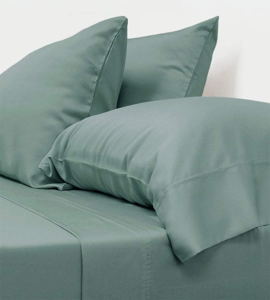 A bed with green sheets on it and two pillows with matching green cases
