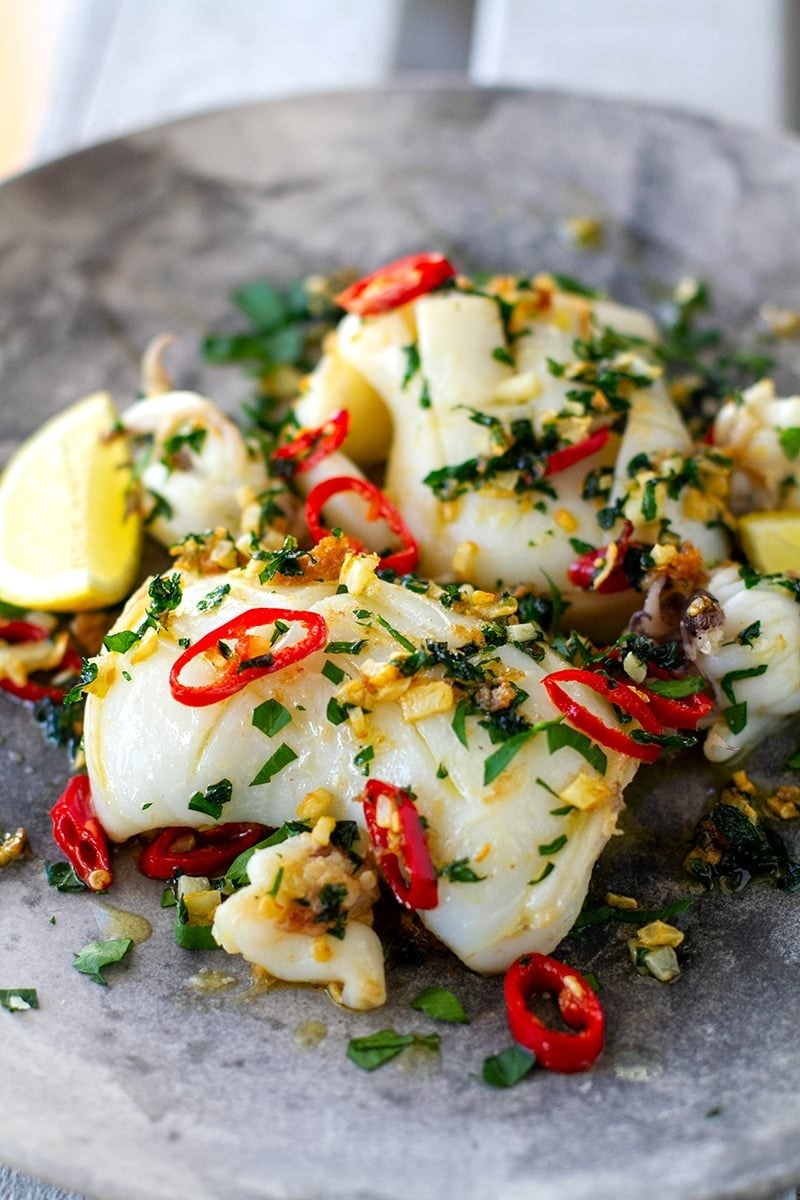 A plate of grilled squid surrounded by sliced red chili peppers, parsley, and crispy garlic.